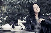 Young fashion woman drinking tea at sidewalk cafe