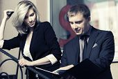 Young business couple with a folder at the office window