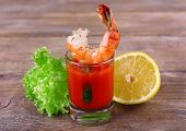 Fresh boiled prawns with lettuce and lemon in a glass with tomato sauce on wooden background