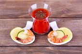 Fresh boiled prawns in a small oval bowl with handle on wooden background