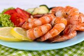 Plate of fresh boiled prawns with tomatoes, lettuce, lemon and avocado on a napkin on wooden background
