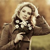 Young fashion woman with a flowers on nature
