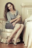 Beautiful fashion woman with long curly hairs in a bedroom