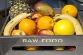 Fresh organic fruit in wooden box ,  RAW FOOD text