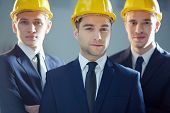 Portrait of three serious businessmen in hardhats