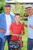 Grandpa, father and boy grilling sausages