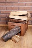 Wooden box of firewood on floor on brick background