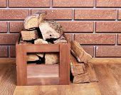 Wooden box of firewood on floor on brick background
