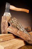 Firewood and axe on floor on dark background