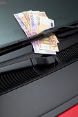 Lots of euros stuck under a windshield wiper symbolizing car expenses
