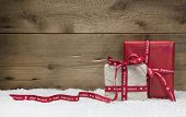 Red And White Christmas Presents, With Snow On Wooden Background For A Greeting Card Or Coupon