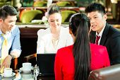 Four Asian Chinese office people or businessmen and businesswomen having a business meeting in a hot