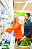 Couple selecting dairy products grocery shopping in supermarket