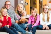 Family sitting together with mother, father and children comfortable on sofa