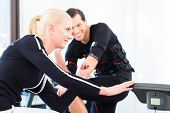 Female coach giving man and woman ems electro muscular stimulation exercise