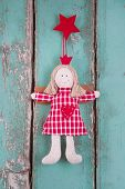 Sewn Angel Doll Hanging On Turquoise Wooden Background For Christmas