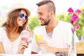 A picture of a happy couple drinking smoothies in an outside cafe
