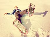 a woman playing in the snow with snow shoes on toned with a retro vintage instagram like filter