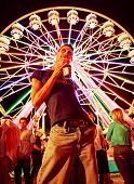 a young man making a funny face at a local state fair at night toned with a retro vintage instagram