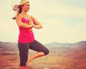 woman meditating in a yoga pose on a hill toned with a soft instagram filter