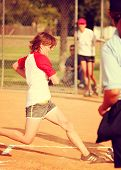 a young girl touching home plate in a softball game toned with a retro vintage instagram filter