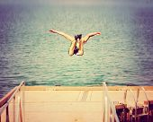 a boy jumping of an old dock into a pond toned with a retro vintage instagram filter