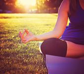 hands of a woman meditating in a yoga pose on the grass toned with a retro vintage instagram filter