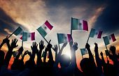 Group of People Waving Mexican Flags in Back Lit