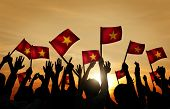 Group of People Waving Vietnamese Flags in Back Lit