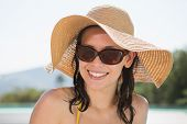 Close up portrait of a cheerful young woman wearing hat on a sunny day