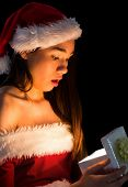 Amazed brunette in santa outfit opening a gift on black background