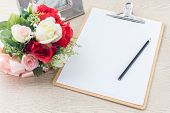 Wooden Clipboard Attach Planning Paper With Pencil Beside Rose Bouquet On Table
