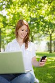 Pretty redhead using her laptop while texting in the park on a sunny day