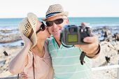 Happy casual couple taking a selfie by the coast on a sunny day