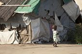BOR, SOUTH SUDAN-DECEMBER 3 2010:Unidentified malnourished child walks past the shack she and her fa