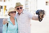 Happy tourist couple taking a selfie in the city on a sunny day