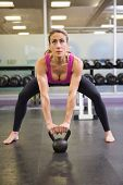 Full length of a serious young woman lifting kettle bell in the gym