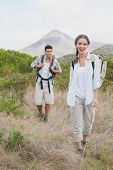 Portrait of hiking young couple walking on countryside landscape
