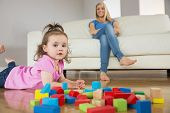 Portrait of a girl playing with building blocks on floor while mother sitting on conch at home