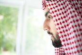 Arabic young sheikh looking trough the window