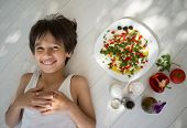 Kid enjoying summer organic kitchen preparing food with vegetable ingredients and creamy cheese