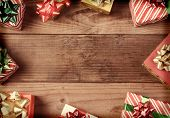 A high angle view of a group of Christmas presents on a rustic wooden floor. The presents are scatte