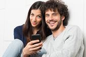 Happy Young Couple Holding Cellphone Looking At Camera
