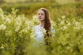 stock photo of beatitudes  - Happy young woman with eyes closed among the wildflowers - JPG