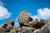 Stone pebbles stacked on the rocks on the beach in Aruba in a simple artistic statement of beaty in nature, zen and meditation under a sunny blue tropical summer sky