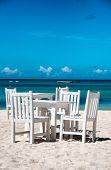 Idyllic outdoor dining on a tropical beach in Aruba with fresh white painted wooden table and chairs