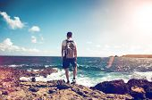 Young man wearing a backpack standing on rocks overlooking the ocean looking down at the white surf