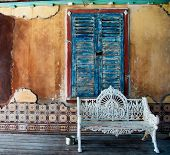 Ornate white wrought iron bench standing on a wooden floor or deck in front of a window with closed
