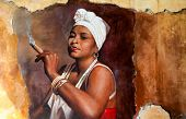 Graffity of Woman wearing a head scarf and traditional jewellery smoking a big fat Cuban cigar with