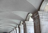 Architectural background of a fluted vaulted ceiling on an exterior walkway supported by a row of re